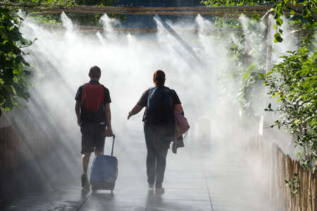 Strasbourg - France - 11 July 2021 - Portrait of people walking in urban park in sprayer installation in front of the train station