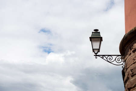 Closeup of vintage street light in the street on cloudy sky background