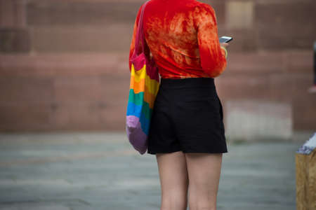 Closeup of lesbian girl standing in the street with rainbow bag Stock Photo