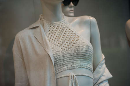 Closeup of beige summer clothes on mannequin in a fashion store showroom