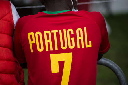 Closeup of african kid wearing a soccer shirt from portugal with the seven number in the street