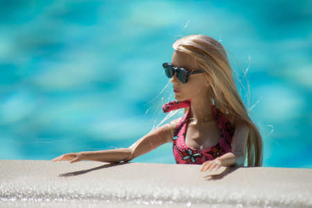 Mulhouse - France - 21 July 2021 - Portrait of blond barbie doll wearing a pink bikini and sunglasses in the swimming pool by sunny day Editorial