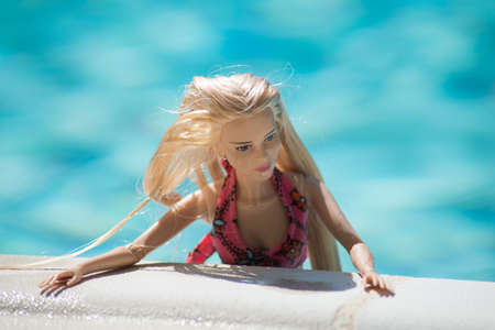 Mulhouse - France - 21 July 2021 - Portrait of blond barbie doll wearing a pink bikini in the swimming pool by sunny day