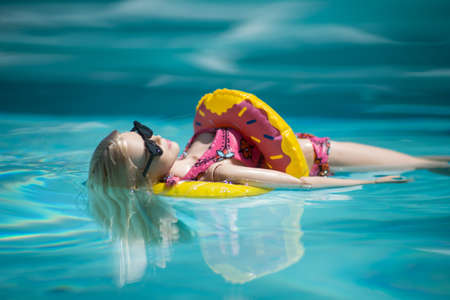 Mulhouse - France - 21 July 2021 - Portrait of blond barbie doll wearing a pink bikini, buoy and sunglasses floating  in the swimming pool by sunny day