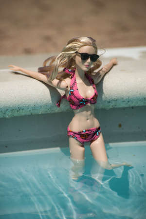 Mulhouse - France - 21 July 2021 - Portrait of blond barbie doll wearing a pink bikini and sunglasses standing in the swimming pool by sunny day Editorial