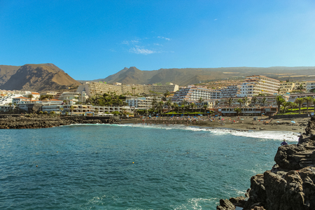 View of the Playa de la Arena and volcanic mountains on the west coast of the Tenerife island, with black sand and lava cliffs at beautiful laguna. Sunny day, clear blue sky with little clouds.