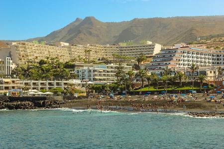 Vue sur la Playa de la Arena et les montagnes volcaniques de la côte ouest de l'île de Ténérife, avec du sable noir et des falaises de lave dans la magnifique lagune. Journée ensoleillée, ciel bleu clair avec de petits nuages.