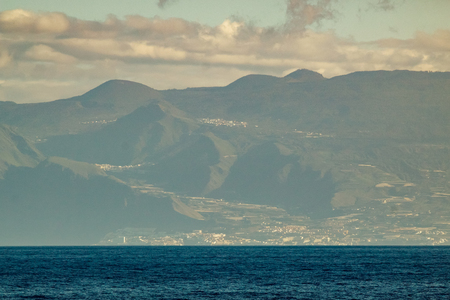 Western part of Tenerife seen from Gomera. Long lens shot. Blue sky with clouds, blue water under straight coast line. Canary Islands, Spain