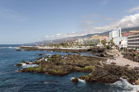Lava rocks and cliffs along coast line in the center of Puerto de la Cruz. Lagos Martianes in the background. Blue sky and beautiful clouds above mountains and hills of La Orotava valley. Tenerife, Spain