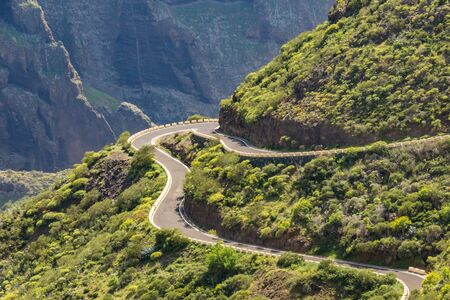 Serpentine road and amazing view of mountain landscape in a sunny day on tropical island. Road adventure trip on the Canary Islands. Long focus. Stok Fotoğraf