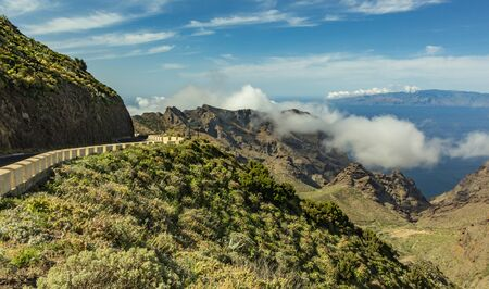Serpentine road and amazing view of Blue sky with beautiful fluffy clouds, Island of La Gomera, mountain landscape. Sunny day on tropical island. Road adventure trip on the Canary Islands. Wide angle.