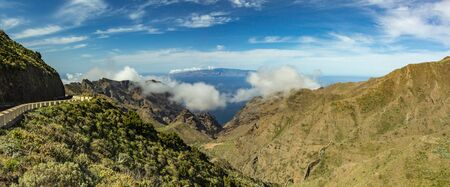 Serpentine road and amazing view of Blue sky with beautiful fluffy clouds, Island of La Gomera, mountain landscape. Sunny day on tropical island. Road adventure trip on the Canary Islands. Wide angle. Panorama.