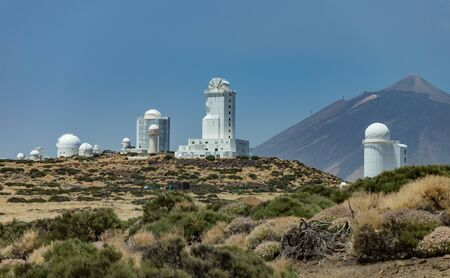 International observatory in Teide National Park. Volcano Teide on the backgriund. Windy day with clouds and amazinc colors. Technology science concept.