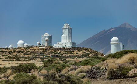 Observatorio internacional en el Parque Nacional del Teide. Volcán Teide en el backgriund. Día ventoso con nubes y colores asombrosos. Concepto de ciencia tecnológica.
