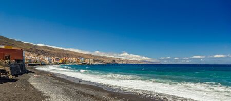 Coast line with long black sand beach in the town Candelaria in the eastern part of Tenerife in the Spanish Canary Islands. Stock Photo