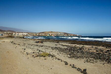 Beautiful coastal view of El Salado - Salted Beach. Shining clear blue sky over Horizon line, wave ripples on the turquoise water. El Medano, Tenerife. Stock fotó