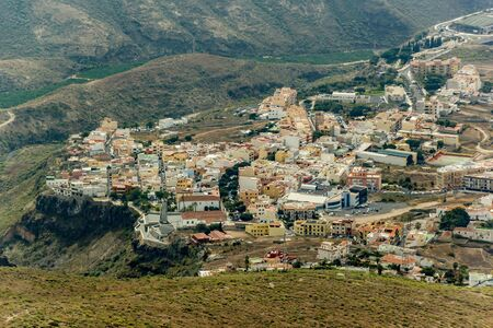 Aerial view of Adeje town on the soth coastline at sunny day. Beginning of famous Hell gorge. Rocky tracking road in dry mountain area. Tenerife, Canary Island.