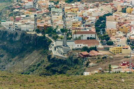 Aerial view of Adeje town on the soth coastline at sunny day. Beginning of famous Hell gorge. Rocky tracking road in dry mountain area. Tenerife, Canary Island. Zdjęcie Seryjne - 128906812