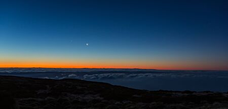 Morning dark sunrise with blue sky and golden yellow orange color above horizon. Night lights of Gran Canaria Island between clouds. with overlook of young moon and Venus.