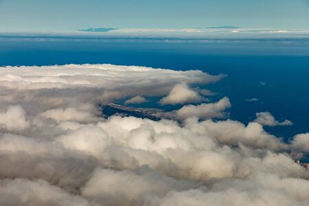 Panoramic view to Puerto de la Cruz and Orotava valley. Above wight fluffy clouds, clear blue sky and small part of La Palma island in the line of horizon. Spain, Canary Islands, Tenerife.