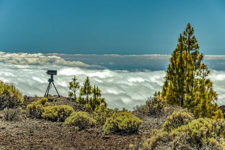 Mountains and pine tree forest near volcano Teide, partly covered by the clouds. Bright blue sky. Telescope on the tripod ready observing the sun. Tenerife, Canary Islands, Spain. 1800m altitude. Stok Fotoğraf