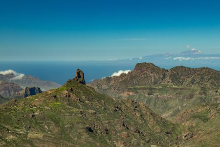 Center of Gran Canaria. Spectacular aerial view across Caldera de Tejeda towards Teide on Tenerife. Famous Roque Bentayga on average and Tenerife above the horizon with volcano Teide covered by snow.