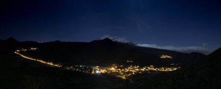 Panoramic View of Santiago del Teide valley at night. The night lights of the city streets and the snow-capped Mount Teide illuminated by the full Moon in the background. Tenerife. Long exposure.