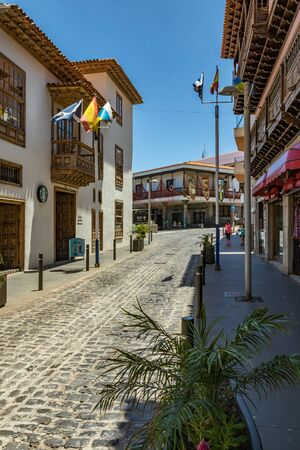 Puerto de la Cruz, Tenerife, Spain - July 10, 2019: Colourful houses and palm trees on streets. People relax and have fun on a warm sunny summer day. Have breakfast, drink coffee in a cozy cafe. Banco de Imagens