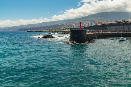 Puerto de la Cruz, Tenerife, Spain - July 10, 2019: . The Old port of town is a popular tourist attraction and favorite place for the locals. We see the harbor and mountains in the surrounding area. Stock fotó