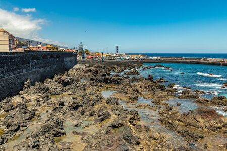 Puerto de la Cruz, Tenerife, Spain - July 10, 2019: . The Old port of town is a popular tourist attraction and favorite place for the locals. We see the harbor, walking and bathing people.