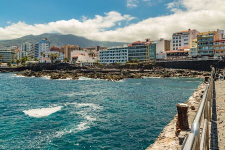 Puerto de la Cruz, Tenerife, Spain - July 10, 2019: . The Old port of town is a popular tourist attraction and favorite place for the locals. We see the harbor and mountains in the surrounding area.