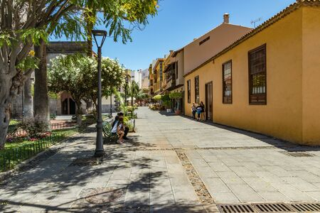 Puerto de la Cruz, Tenerife, Spain - July 10, 2019: Colourful houses and palm trees on streets. People relax and have fun on a warm sunny summer day. Have breakfast, drink coffee in a cozy cafe. Redactioneel