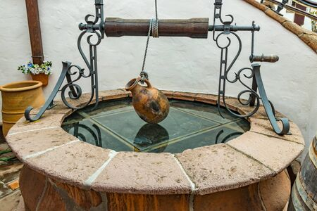 Old earthenware jug hanging on a rope above a rustic well in a vinery of Tenerife, Canary Islands, Spain. Stock Photo