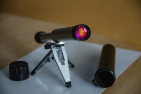 Spyglass on a small tabletop stand. Enlightenment lens beautifully shimmers colors. Black plastic case with open lid. Selective focus close up.