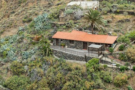 Northeast of La Gomera. Rural house surrounded by palm trees in the garden. Old volcanic mountains covered by green grass, laurels and heather on steep slopes. Canary Islands. Imagens