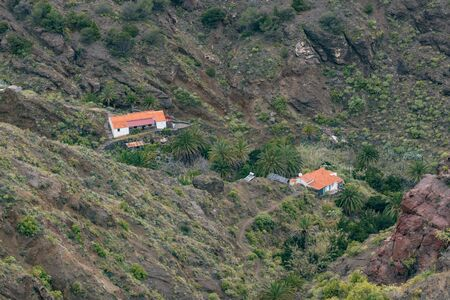 Northeast of La Gomera. Rural house surrounded by palm trees and solar panels in the garden. Old volcanic mountains covered by green grass, laurels and heather on steep slopes. Canary Islands.