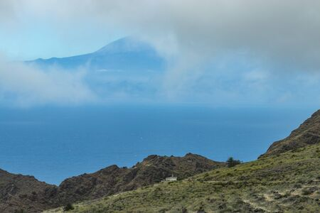 View of Tenerife through low clouds. Parque Natural Majona. Northeastern part of La Gomera Island. Old volcanic mountains covered by green grass, laurels and heather on steep slopes. Canary Islands.