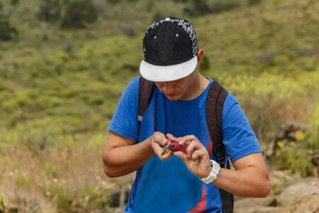 Young guy peels ripe tasty cactus fruit, known as prickly pear or fruit of Opuntia ficus-indica, growing naturally in the dry, arid soil of Tenerife, Canary Islands, Spain. Imagens