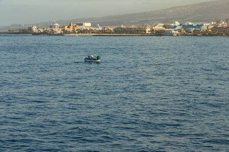 Las Americas, Tenerife, Spain - May 25, 2019: View to the coastline and small fishing boat from the ferry departing for the island of La Gomera early morning from the port of Los Cristianos.