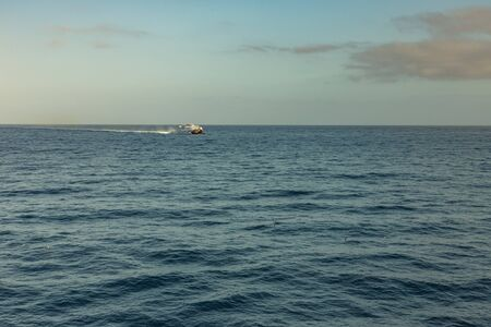 Las Americas, Tenerife, Spain - May 25, 2019: View to the small high-speed ferry from another ferry departing for the island of La Gomera early morning from the port of Los Cristianos. Stok Fotoğraf
