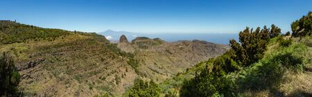 Panoramic view of Tenerife Island with volcano Teide above horizon and Los Roques peaks near Garajonay national park at La Gomera. Thickets of relic laurels and heather on steep green slopes. Canary.