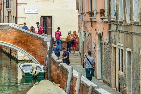 Venedig, Italien - 02. August 2019: Enge Fußgängerzonen von Venedig. Einheimische und Touristen flanieren entlang der historischen Gebäude, Schaufenster, Souvenirs, Cafés und Restaurants.
