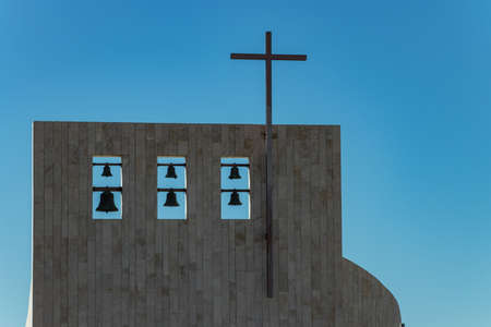 Cross on church over clear blue sky. Six bells of different sizes on the top. Adeje village, Tenerife, Spain