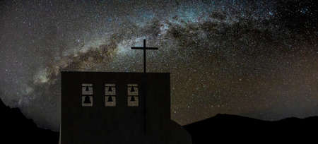 Cross on church over clear night sky and bright Milky Way . Six bells of different sizes on the top. Peaks of high mountains in the background. Reklamní fotografie