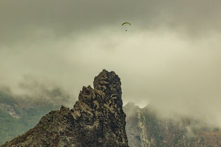 Lonly paraglider between low dense clouds and mountain peak near village of Garachico, Tenerife, Spain.