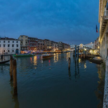 VENICE, ITALY - August 02, 2019: View from Rialto Bridge in Venice at sunset time. Venetian Grand Canal with historical buildings, hotels, tourist boats, piles, berths. Fish eye lens shot.