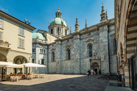 Como, ITALY - August 4, 2019: Local people and tourists on a quiet cozy streets near Cathedral in the beautiful Italian Como city. Warm sunny summer day in very popular holiday destination.
