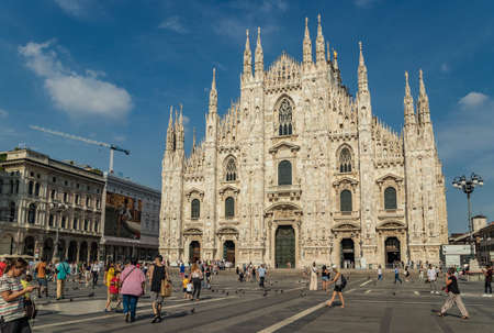 MILAN, ITALY - AUGUST 1, 2019 : The piazza, looking roughly north-east to the facade of Duomo. Galleria Vittorio Emanuele II - on the left.