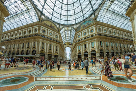 MILAN, ITALY - AUGUST 1, 2019: Famous Galleria Vittorio Emanuele II in a beautiful summer day in Milan. Tourists and locals walk among Shops, boutiques, cafes.
