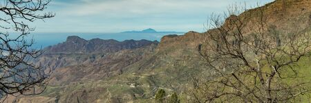 Super wide panorama. Aerial view of the center of Gran Canaria. Famous Bentayga rock in huge caldera and the island of Tenerife with beautifull volcano Teide above the horizon.
